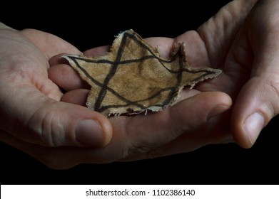 Closeup of a ragged Jewish badge in the hands of a man