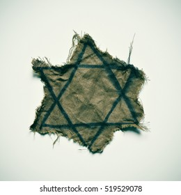closeup of a ragged Jewish badge on an off-white background