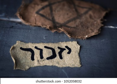 closeup of a ragged jewish badge and a yellowish piece of paper with the word yizkor, remember in hebrew and the name of a prayer in memory of deceased beloveds, on a gray rustic wooden surface