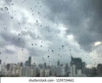 Closeup rain drops on window glass with gray clouds and city view background.