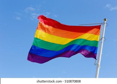 Closeup of a rainbow flag on blue sky.
