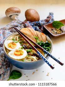 Closeup of Ramen soup with chicken breast, mushrooms and spinach in a bowl with chopsticks on top in a morning light