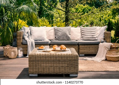 Close Up Of A Rattan Outdoor Table With Coffee And Croissants On It In Front