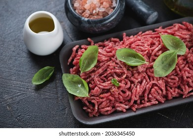 Close-up of raw beef mincemeat with fresh green basil, pink salt and olive oil, studio shot on a dark-brown stone surface
