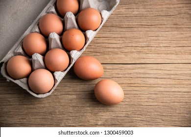 Closeup of raw chicken eggs in egg box on brown wooden background, organic food from nature good for health