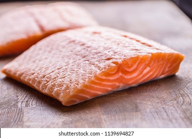 Close-up raw salmon fillets on wooden table.