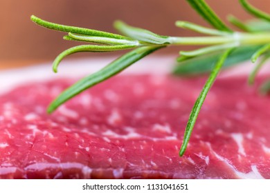 closeup of raw steak with rosemary