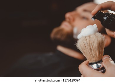 Close-up razor in hands of barber, background client is waiting for shaving his beard and mustache.
