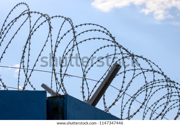 Closeup of razor wire on the top of the wall
