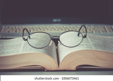 Closeup of reading glasses on the book.