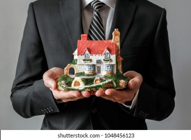 Closeup of real estate agent holding a house in his hand. Real estate business.