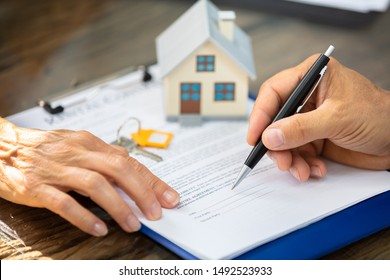 Close-up Of A Real Estate Agent's Hand Helping Client In Filling Contract Form Over Desk