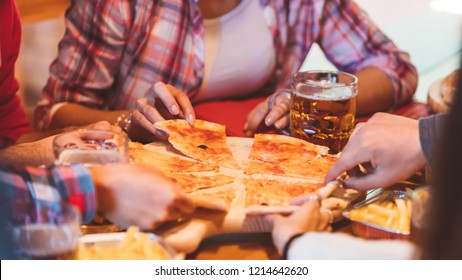 Close-up of real Italian pizza on table and  group of young college friends sitting around and picking up a slice. Best friends having fun together at party with pizza.