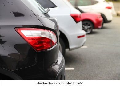 Closeup of rear, back side of black car with  other cars parking in outdoor parking area in rainy day. The mean of simply transportation in modern world.