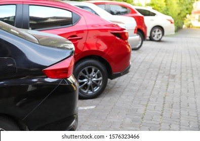 Closeup of rear, back side of black car with  other cars parking in outdoor parking area with natural background in sunny day.
