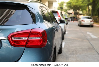 Closeup of rear or back side of blue car with  other cars parking in parking area beside the street in sunny day. The mean of simply transportation in modern world.