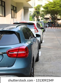 Closeup of rear or back side of blue car with  other cars parking in parking area in sunny day. The mean of simply transportation in modern world. Vertical view.