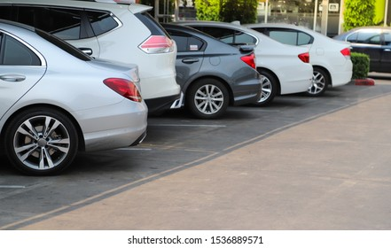 Closeup of rear, back side of soft blue car with  other cars parking in parking lot under the roof in bright sunny day. The mean of simply transportation in modern world.