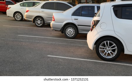 Closeup of rear, back side of white car with other cars parking in outdoor parking lot in the evening of sunny day. The mean of simply transportation in modern world.