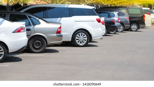 Closeup of rear, back side of white car with  other cars parking in outdoor parking lot in bright sunny day. The mean of simply transportation in modern world.