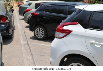 Closeup of rear, back side of white car with  other cars parking in outdoor parking lot beside the street in bright sunny day. The mean of simply transportation in modern world.