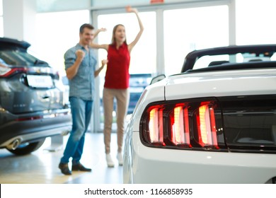 Closeup of rear headlights of new expensive car in auto salon. Happy handsome male and redhaired beautiful woman standing near automobile, jumping and rejoicing in purchase on background.