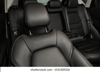 Close-up rear seat made of black leather with a head restraint, in the background passenger seats with seat belts. Luxury car interior - Shutterstock ID 1531309226
