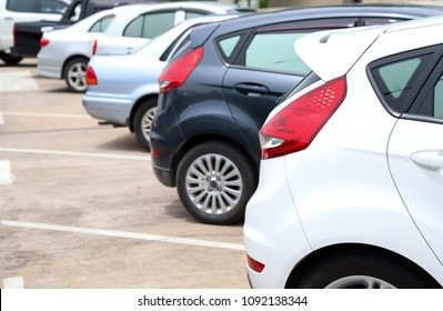 Closeup of rear side of white car and other park in parking area beside the street with natural background in sunny day.