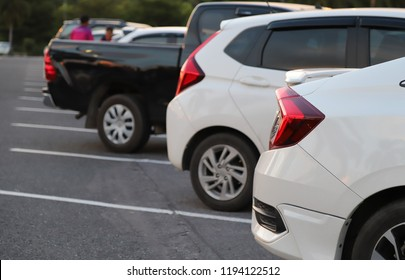 Closeup of rear side of white car park in parking area with natural background in the evening of sunny day.