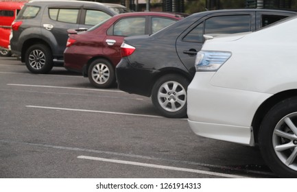 Closeup of rear side of white car parking in parking lot with natural background in the evening twilight.