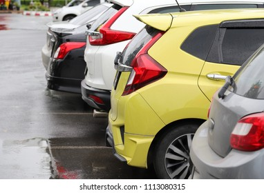 Closeup of rear side of yellow car park in parking area with natural background in rainy day.