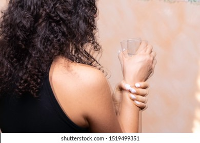A closeup and rear view of a girl suffering from Parkinson's disease, violently trembling and holding her wrist trying to be steady, involuntary movements symptomatic of the disease.