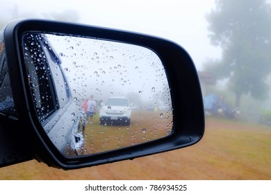 Closeup Rear view mirror to camping on mist and rain