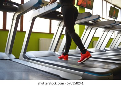 Close-up rear view shot of athletic woman legs jogging on treadmill in front of window at gym before workout. Sport and fitness concept