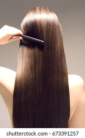 Closeup rear view of a woman combing her long brown hair against gray background