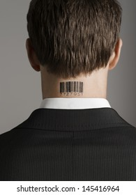 Closeup rear view of a young businessman with bar code tattoo on his neck against gray background