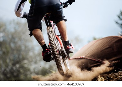 closeup of rear wheel of bike extreme racer on track downhill, dust from wheels