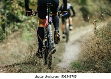 closeup of rear wheel sports mountainbike rides on road in woods