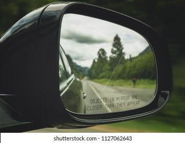 Close-up of a rearview mirror with the text Objects in mirror are closer than they appear. Car on the road.