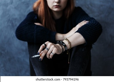 Close-up of rebellious girl wearing black clothes and smoking a cigarette