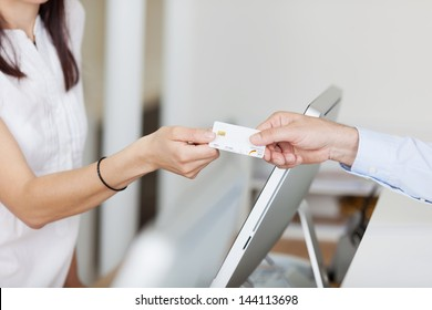 Closeup of receptionist receiving card from male patient in dentist clinic