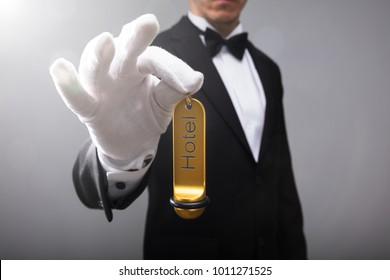 Close-up Of A Receptionist's Hand Holding Hotel Door Key
