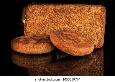 closeup rectangular rye bread with sesame seeds decoration and two cereal flapjacks served on black background