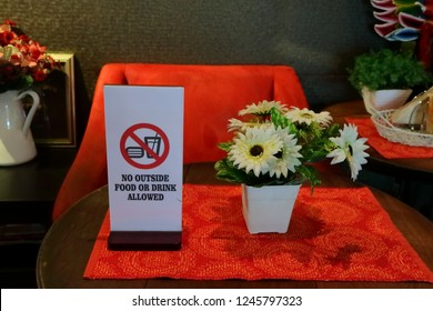 closeup of rectangular sign read no outside food or drink allowed, on red cloth with artificial flowers on round wooden table