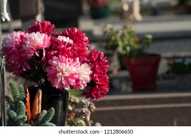 closeup of red artificials chrysanthemums on tomb in cemetery