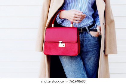 Closeup red bag purse in hand of young woman. Casual fall fashion outfit