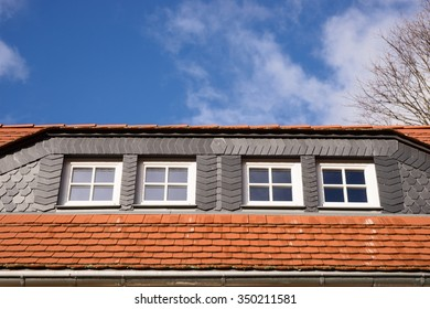 Closeup of red and black roof tiles with windows