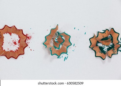 Close-up of red, blue and green colored pencil shavings on white background