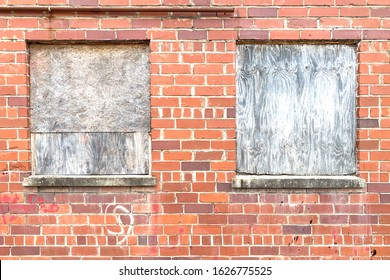 closeup of a red brick wall with boarded up windows