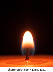 Close-up of a red candle flame on a black background
